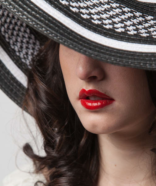 Woman with red lips, eyes shaded by hat